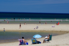 Cape Cod attractions like this photo of the Head of the Meadow sandbar at low tide with sunbathers, swimmers and beach umbrellas are what bring visitors back to Cape Cod each year