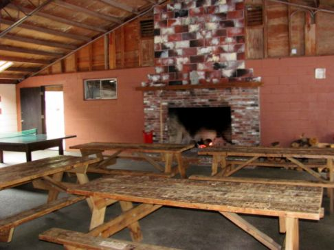 photo of the large recreation building at North of Highland campgrounds on Cape Cod, photo insert image shows the huge fireplace and picnic tables and ping pong inside the rec hall