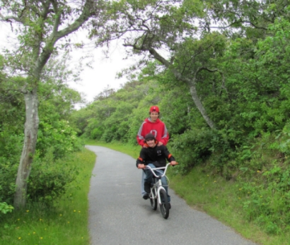 photos of tourists riding bikes along the Head of the Meadow Bike Trail with views of the Cape Cod sandunes and inlet marsh in the background