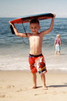 photo of a young boy carrying his boogie board from the beach near North of Highland Camping Area