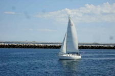 photo of sailboat in the Cape Cod harbor with barrier wall in background