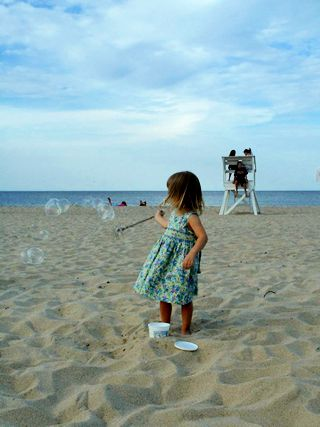 photo of a young girl blowing bubbles on the Cape Cod beach