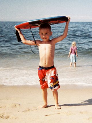 Smiling boy carrying a boogie board out of the ocean at Head of the Meadow Beach