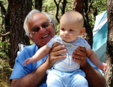 photo of grandfather holding baby in his campsite in North of Highland campgrounds on Cape Cod
